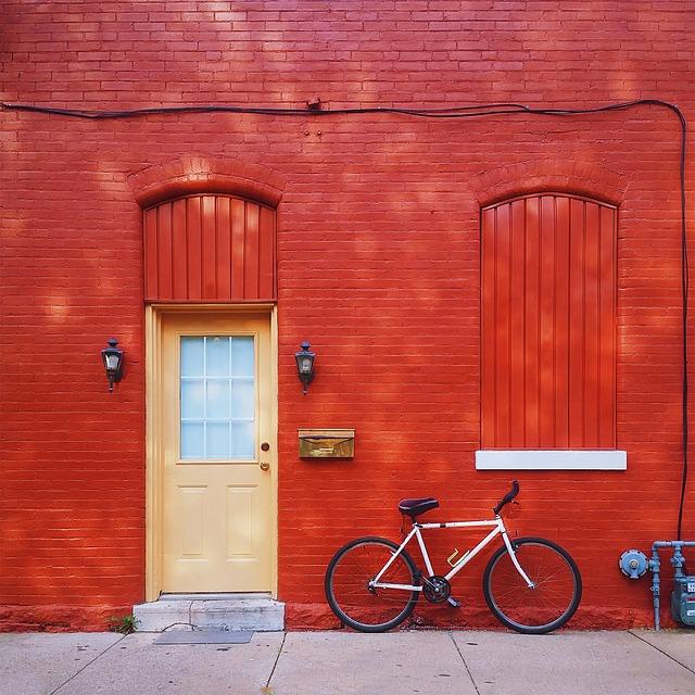 červená zeď, světlé dveře, kolo