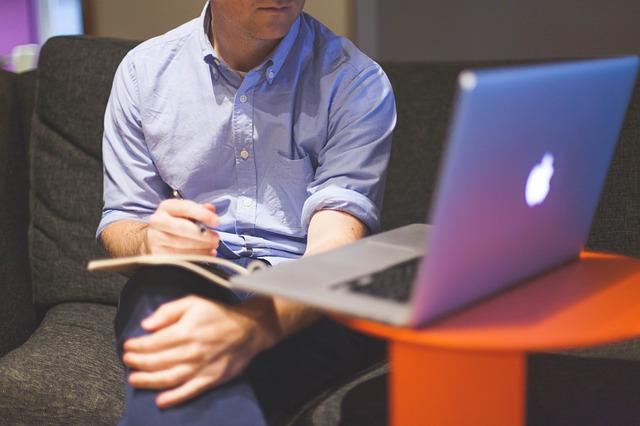 muž, který si něco zapisuje do sešitu podle počítače