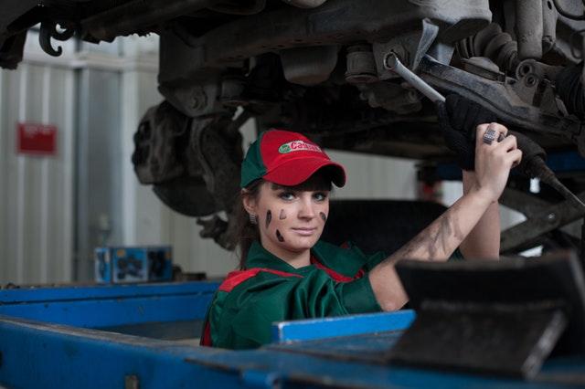 žena, která má auto na rampě a opravuje