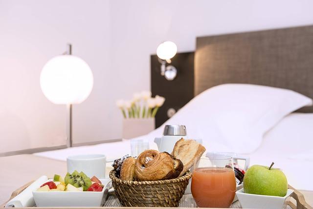 snídaně v posteli, jablko, džus, pečivo, ovoce v miskách a za tím postel a polštář