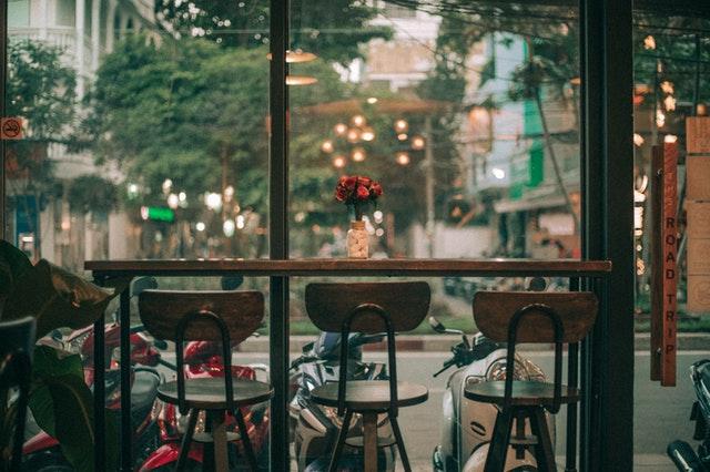 Řada židlí v baru postavených před oknem-výlohou
