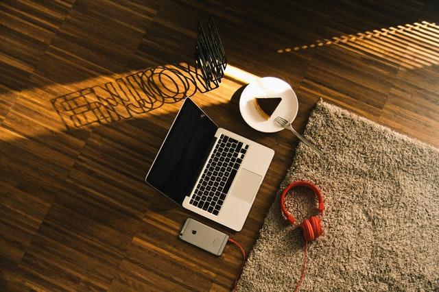 notebook na dřevěné podlaze, dort